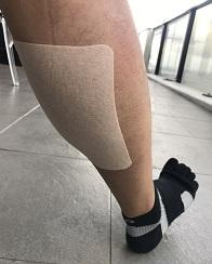 足の筋肉でシップを貼る様子